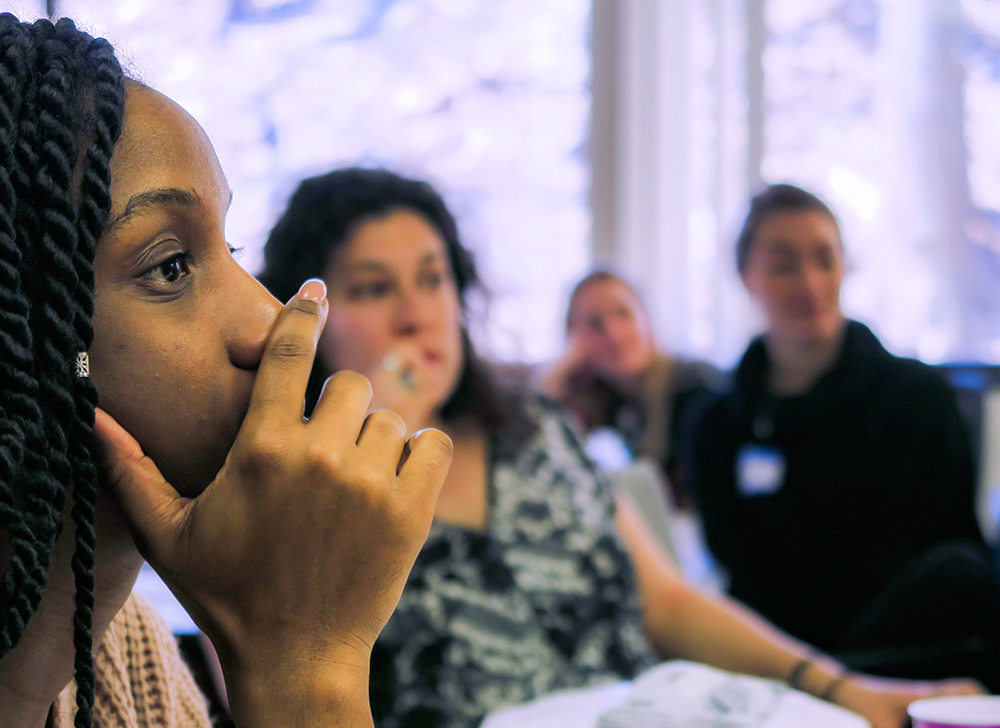 Female participants listen to a behavioral health training.